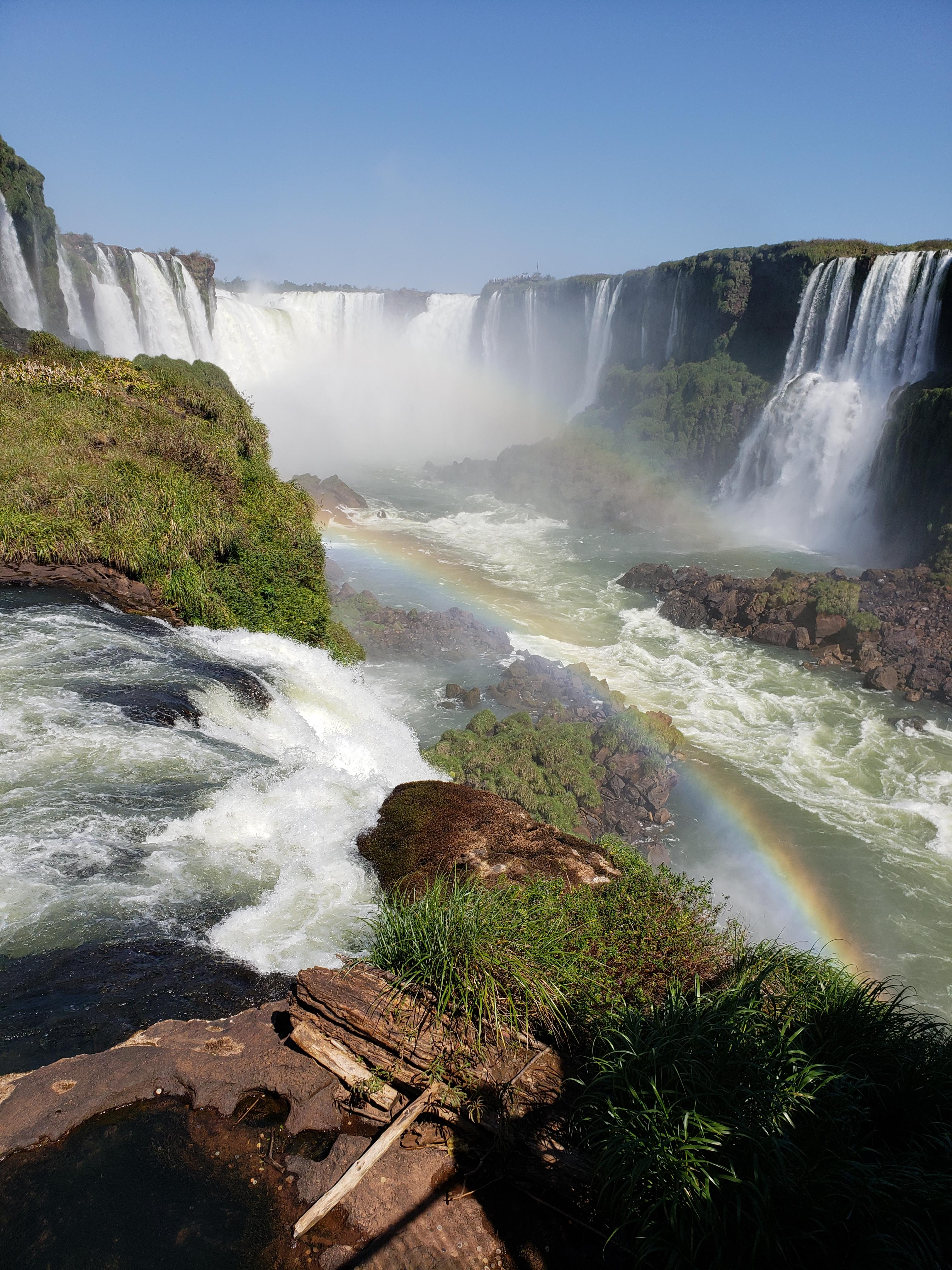 Iguasso Falls, Brazil. The water tumbles over cliffs, forming rainbows in the sunlight.